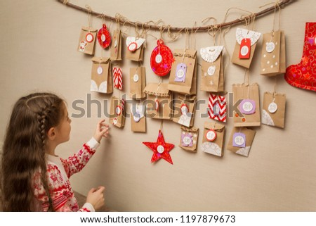 child looks at the advent calendar. option DIY to wait for Christmas for kids.