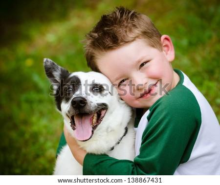 Child lovingly embraces his pet dog, a blue heeler #138867431
