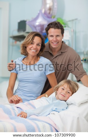 Child lying on a medical bed next to his parents in hospital ward