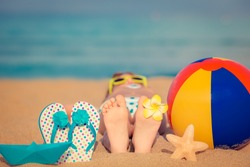 Child lying on sandy beach near blue sea. Summer vacation and healthy lifestyle concept