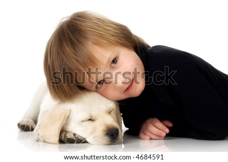 Child lying with head on sleeping Labrador retriever puppy