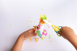 child makes a parrot craft from paper and recycled yogurt bottle, DIY . Kindergarten or school children activity, funny bird craft for kids, kids hands hold scissors