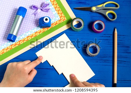 Child makes card with 3D gifts for Christmas. Children's art project. DIY concept. Step by step photo instruction. Step 4. Fold paper along cut lines