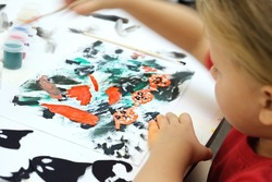 Child making abstract card for the  halloween. Funny crafts from paper. Halloween decor. The concept for Halloween. DIY. Children's art project. Shallow DOF