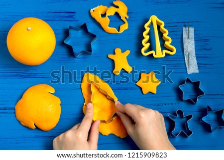Child making decorations of orange peel for Christmas. Children's art project. DIY concept. Step by step photo instruction. Step 2. Cut figures using cookie cutters