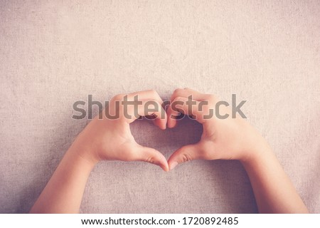 child making heart shape hands, heart health, generous, love and kindness, sustainable living, donate, charity, young volunteer, csr responsible business concept Photo stock ©