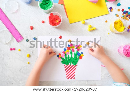 Child making homemade greeting card. little girl making vase with flowers from paper and clay, plasticine as gift for Mothers day, Birthday or Valentines day . Arts  crafts concept.
