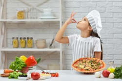 child making tasty delicious gesture by kissing fingers. little girl in chef hat and an apron cooking pizza in the kitchen.