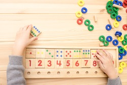 Child math development, learning center, primary school, sorting skills concept. Hands of a Caucasian child playing with a wooden math toy. Number line, counting 1-10. Top view. Desk. Horizontal.