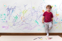 Child mischief. Boy with a distracted face because he drew the entire wall. Little boy leaning against the white wall where he made many drawings with colored pencils. Kid indoors, at home.