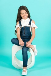 Child model in jeans overall sit leg crossed on chair. Girl with long healthy brunette hair smile on blue background. Kid fashion, style. Beauty, look concept. Youth, skincare, health.