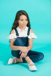 Child model in jeans overall sit on floor. Girl with long brunette hair on blue background. Fashion, style concept. Beauty, look, hairstyle. Childhood, preteen, youth, punchy pastel