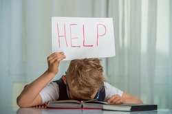 Child needs help with homework. San kid put head on table. Little boy with paper with Help word.