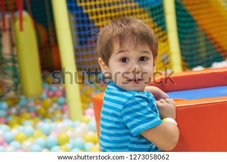 child of three years old is playing in a ball pool. boy smiling spends fun time in the children's room #1273058062