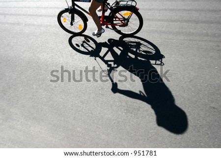 child on  a bicycle with his shade on the road bike race in denmark, cyclist are passing by a bike sign on the road. Shot with low shutter speed to achieve motion blur