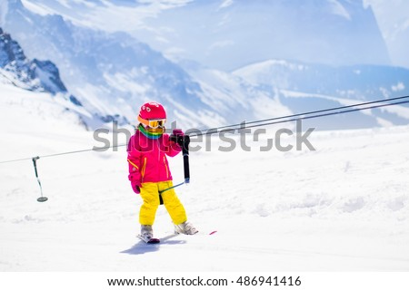 Child on a button ski lift going uphill in the mountains on a sunny snowy day. Kids in winter sport school in alpine resort. Family fun in the snow. Little skier learning and exercising on a slope. #486941416