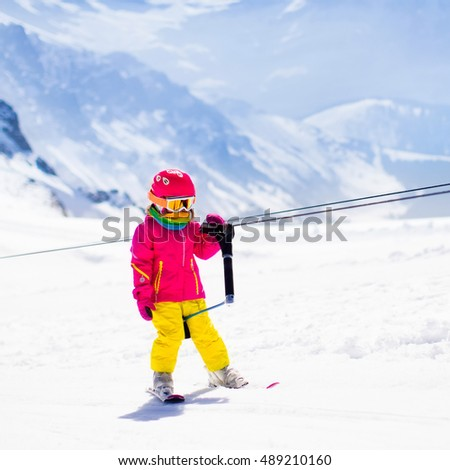 Child on a button ski lift going uphill in the mountains on a sunny snowy day. Kids in winter sport school in alpine resort. Family fun in the snow. Little skier learning and exercising on a slope. #489210160