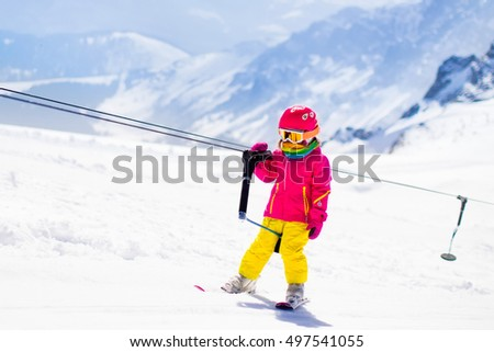 Child on a button ski lift going uphill in the mountains on a sunny snowy day. Kids in winter sport school in alpine resort. Family fun in the snow. Little skier learning and exercising on a slope. #497541055