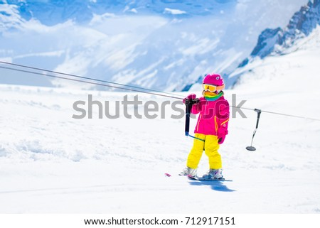 Child on a button ski lift going uphill in the mountains on a sunny snowy day. Kids in winter sport school in alpine resort. Family fun in the snow. Little skier learning and exercising on a slope. #712917151