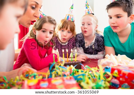 Child on birthday party blowing candles on cake being helped by friends and the mother #361055069