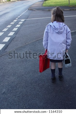 Child on her way to school, getting ready to cross the street.