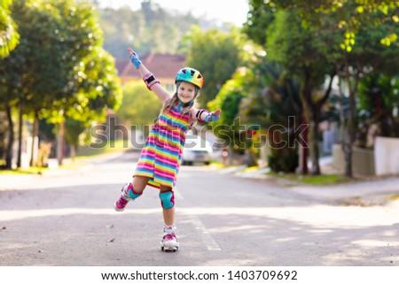 Child on inline skates in park. Kids learn to skate roller blades. Little girl skating on sunny summer day. Outdoor activity for children on safe residential street. Active sport for preschool kid. #1403709692