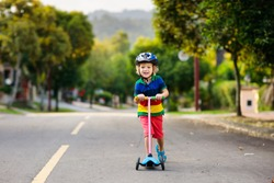 Child on kick scooter in park. Kids learn to skate roller board. Little boy skating on sunny summer day. Outdoor activity for children on safe residential street. Active sport for preschool kid.