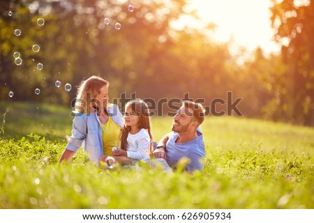 Child on picnic with parents make soap bubbles