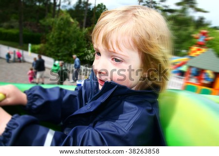 child on ride in them park. toddler on roller coaster at amusement fair - stock photo