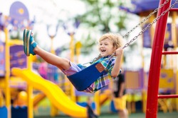 Child on swing playing on outdoor playground. Kids play on school or kindergarten yard. Active kid swinging. Healthy summer activity for children. Little boy having fun outdoors.