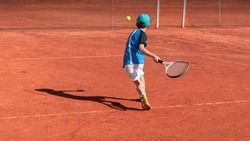 Child on tennis court. Boy tennis player learning to hit forehand . Physical activity and sports education of children. Tennis training at school or club. Background, copy space