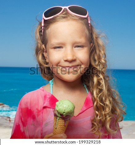 Child on the beach with ice cream. Girl at vacations on sea