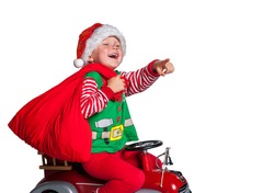 Child on toy car with Xmas bag full of gifts and present. Kid pointing up. Buying christmas gifts - online shopping and delivery concept. Happy smiling boy with Santa costume. New Year and Christmas.