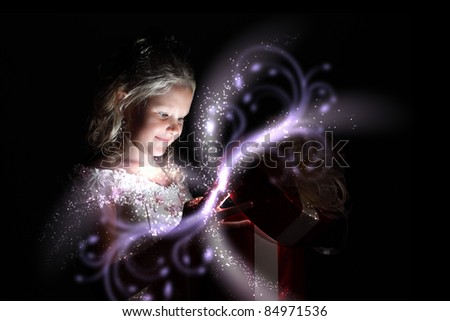 Child opening a magic gift box with lights and shining around