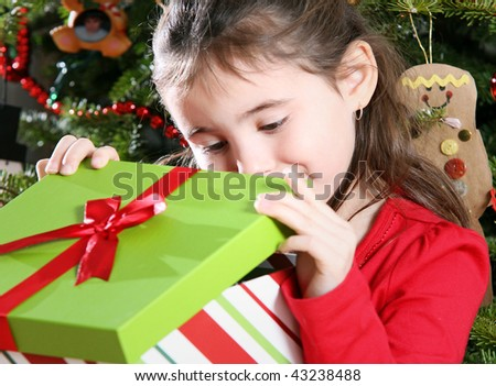 Child opening gifts on Christmas morning - stock photo