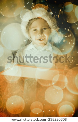 Child opening his christmas present against twinkling red and orange lights