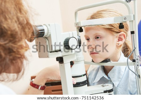 child ophthalmology. female doctor checks eyesight at girl