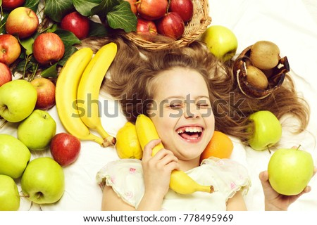 Stock Photo child or cute baby girl laying with colorful fruits hold banana as phone