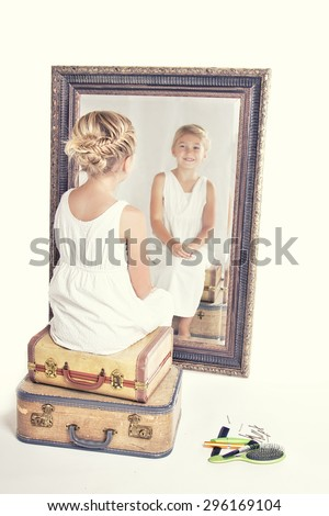 Stock Photo Child or young girl staring at herself in a mirror, sitting on vintage luggage, with a fish tail braid in her hair. Vintage or retro filter applied.