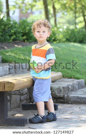 Child outdoors in a park in summer, active and fit, thirsty drinking a juice