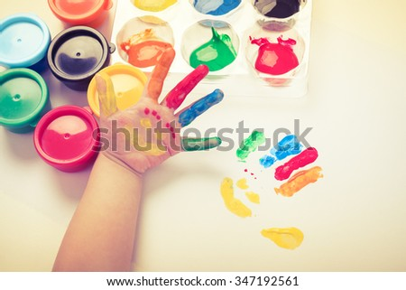 Child paint her palm with smiling face various colors using multicolored drawing tools. Studio shot. Cream tone.