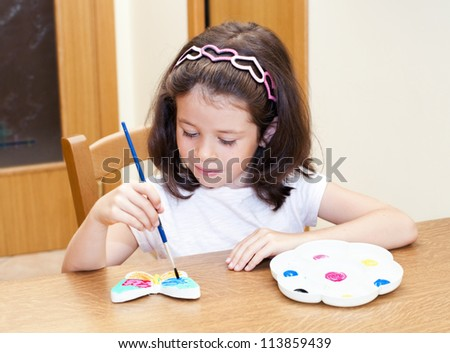 Child painting a butterfly with a color palette