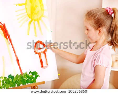 Child painting at easel in school. Education.