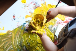 Child painting her hand with yellow paint and paintbrush. Finger painting or art therapy for children. Fun activities for toddlers.