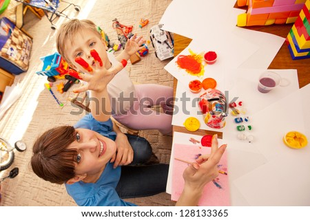 child painting in kindergarten with a teacher. little boy playing with water colors. education.