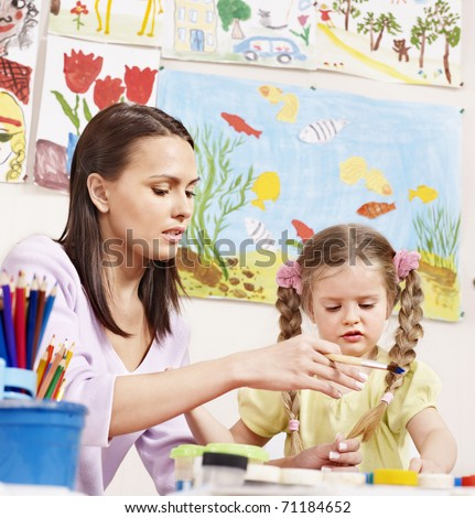 Child painting in preschool. Teacher help by little girl.
