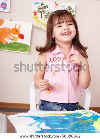 Child painting picture  in play room. Preschool.