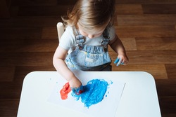 Child painting with her hands on the table at home using blue and red paint. Finger painting or art therapy for children. Fun activities for toddlers. Top view.