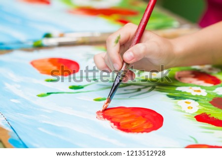 Child paints a picture by gouache. Kid drawing poppies and chamomiles. The hand and paint brush. Closeup, selective focus