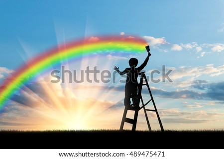 Child paints a rainbow in the sky at sunset #489475471